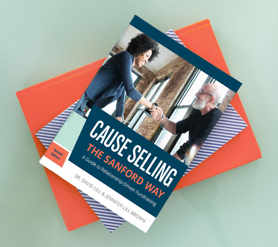 Cause Selling book on a table and a person typing on a laptop